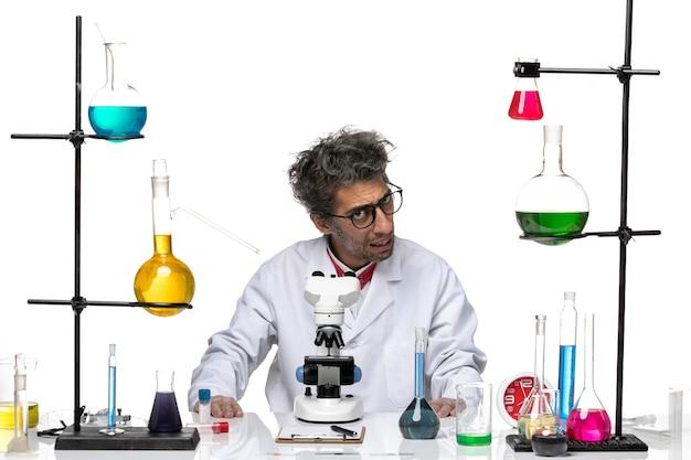 Vue avant de l'homme scientifique en costume médical blanc juste assis