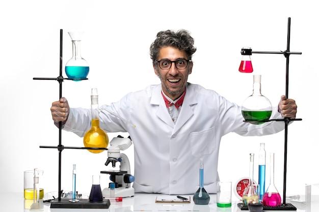 Vue avant de l'homme scientifique en costume médical blanc se réjouissant