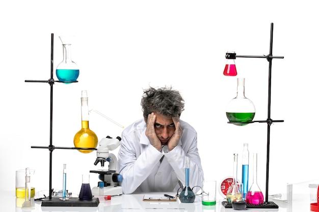 Vue avant de l'homme scientifique en costume médical blanc se sentant tellement épuisé