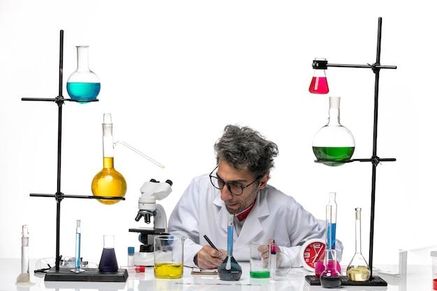 Vue avant de l'homme scientifique en costume médical, écrire des notes