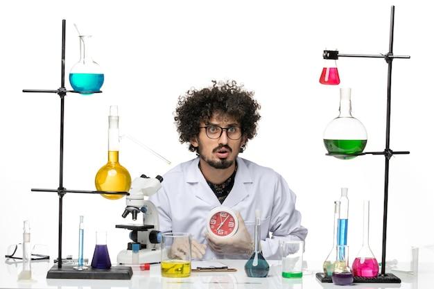 Vue avant de l'homme scientifique en costume médical tenant des horloges rouges sur un bureau blanc