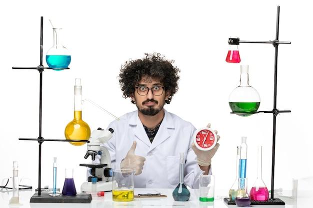 Vue avant de l'homme scientifique en costume médical tenant des horloges rouges sur l'espace blanc