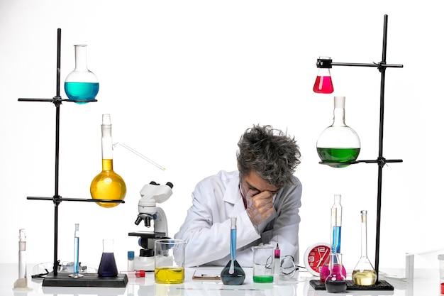 Vue avant de l'homme scientifique en costume médical travaillant avec des solutions se sentant fatigué