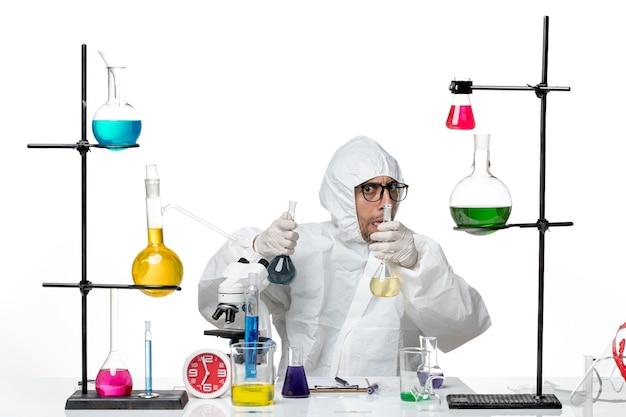 Vue avant de l'homme scientifique en tenue de protection spéciale tenant des flacons avec des solutions
