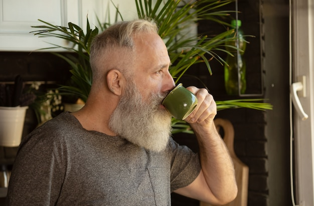Vue avant de l'homme senior barbu avec une tasse de café sur sa cuisine