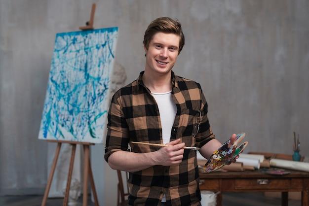 Vue avant homme souriant mélangeant différentes couleurs pour sa peinture