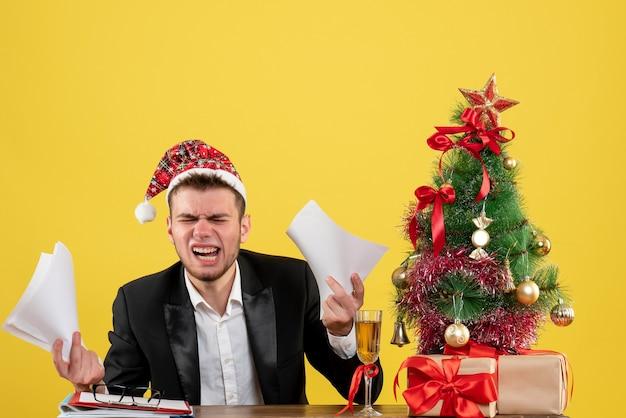Vue avant de l'homme travailleur assis derrière son lieu de travail avec des documents sur le bureau de travail jaune travail de noël couleur nouvel an