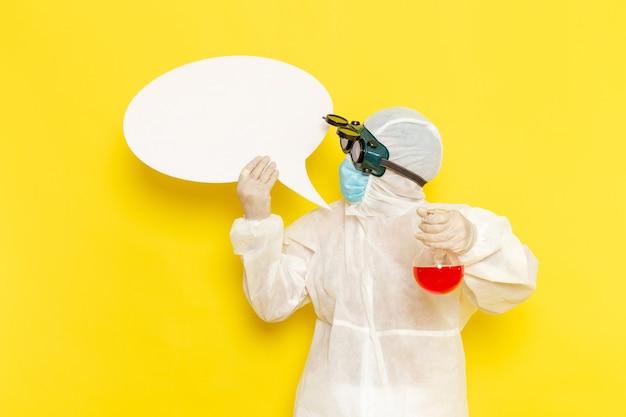 Vue avant de l'homme travailleur scientifique en combinaison de protection spéciale holding flask avec solution rouge et panneau blanc sur sol jaune
