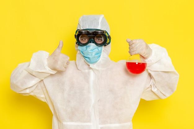 Vue avant de l'homme travailleur scientifique en combinaison de protection spéciale tenant le flacon avec une solution rouge sur un bureau jaune