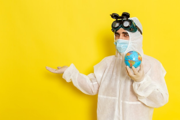 Vue avant de l'homme travailleur scientifique en costume spécial tenant petit globe rond sur un bureau jaune