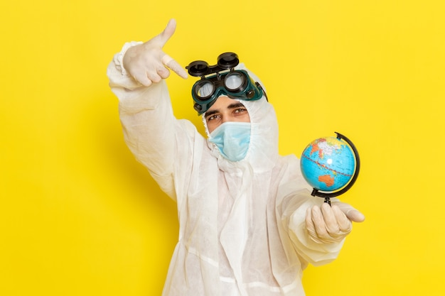 Vue avant de l'homme travailleur scientifique en costume spécial tenant petit globe rond posant sur un bureau jaune