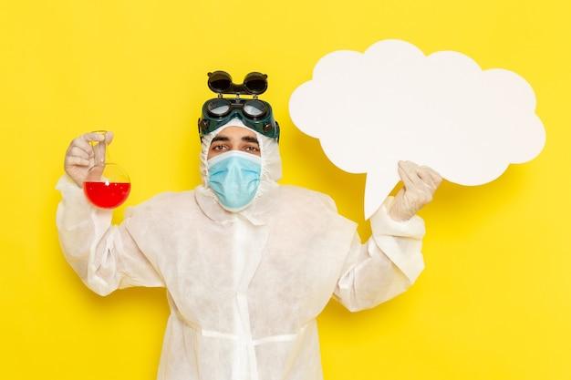 Vue avant de l'homme travailleur scientifique en tenue de protection spéciale tenant le ballon avec une solution rouge grand panneau blanc sur le bureau jaune