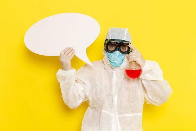 Vue avant de l'homme travailleur scientifique en tenue de protection spéciale tenant le ballon avec une solution rouge et panneau blanc sur un bureau jaune