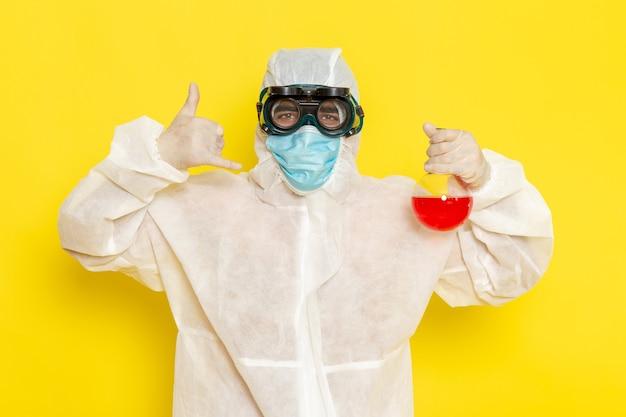Vue avant de l'homme travailleur scientifique en tenue de protection spéciale tenant le ballon avec une solution rouge posant sur la surface jaune