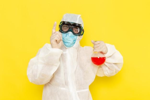 Vue avant de l'homme travailleur scientifique en tenue de protection spéciale tenant le ballon avec une solution rouge sur une surface jaune clair