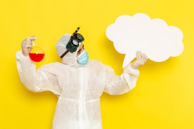 Vue avant de l'homme travailleur scientifique en tenue de protection spéciale tenant le flacon avec une solution rouge et grand panneau blanc sur la surface jaune clair