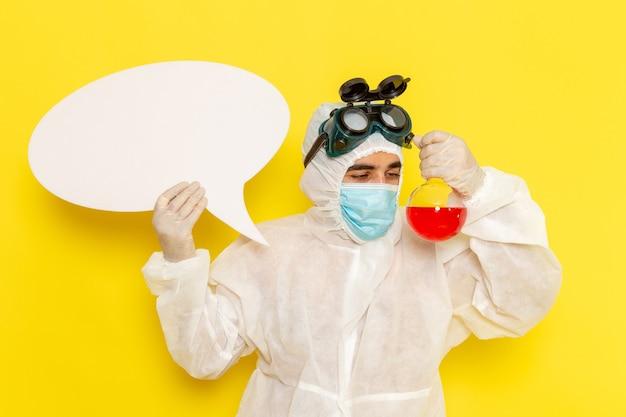 Vue avant de l'homme travailleur scientifique en tenue de protection spéciale tenant le flacon avec une solution rouge et un panneau blanc sur un bureau jaune clair