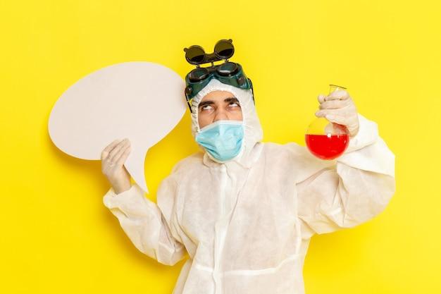 Vue avant de l'homme travailleur scientifique en tenue de protection spéciale tenant flacon avec solution rouge et panneau blanc sur surface jaune