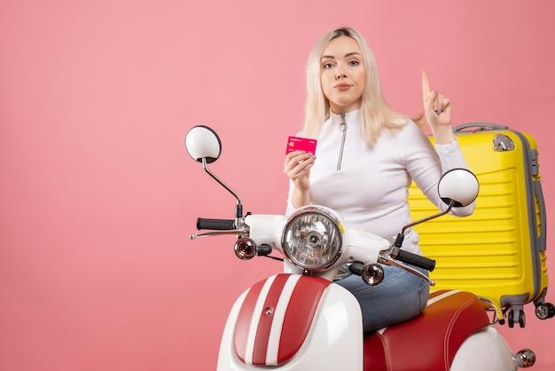 Vue avant, jeune femme, sur, cyclomoteur, tenue, carte, pointage, à, plafond, élégant, rose, mur