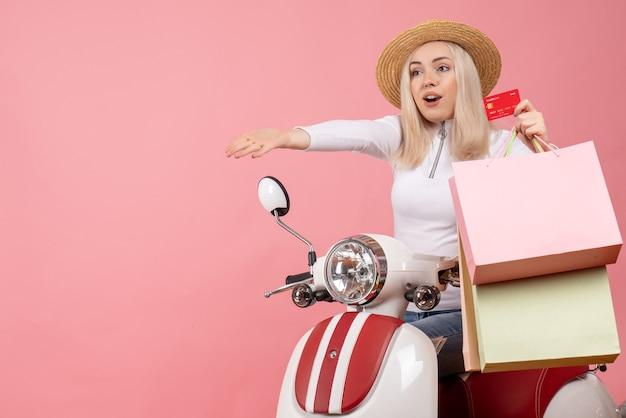 Vue avant, jeune femme, sur, cyclomoteur, tenue, carte, et, sacs provisions