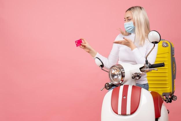 Vue avant, jeune femme, sur, cyclomoteur, à, valise jaune, tenue, carte, sur, mur rose
