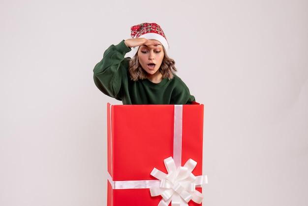 Vue avant jeune femme à l'intérieur de la boîte présente rouge à la recherche
