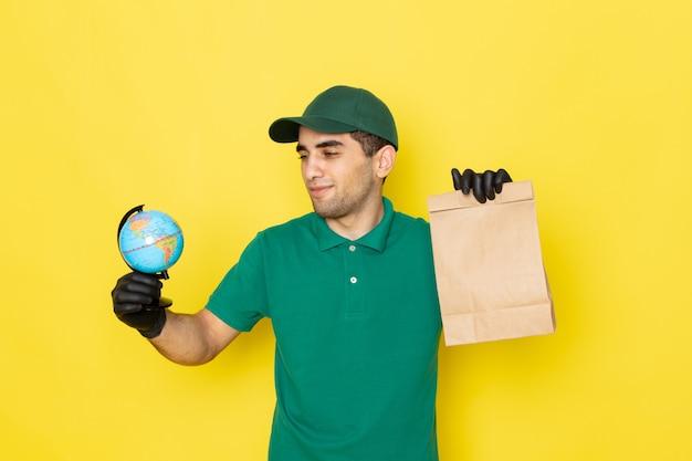 Vue avant, jeune, homme, courrier, dans, chemise verte, chapeau vert, tenue, livraison, paquet, et, globe, sur, jaune