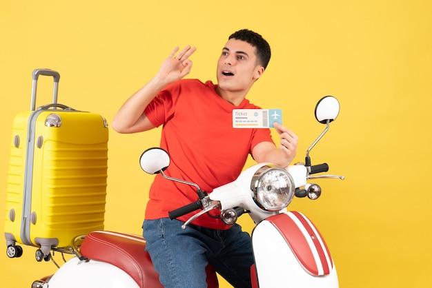 Vue avant, jeune homme, sur, cyclomoteur, tenue, billet, regarder quelque chose, sur, fond jaune