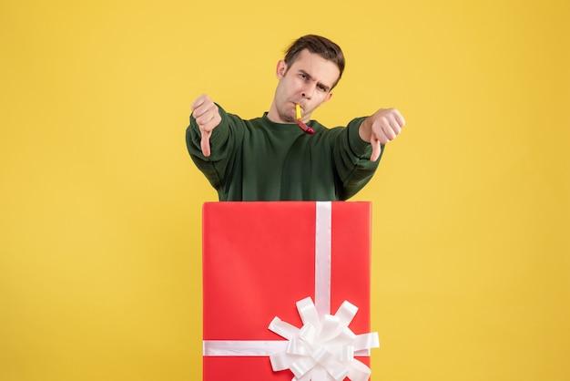 Vue avant, jeune homme, faire, pouce bas, signe, debout, derrière, grand, boîte cadeau, sur, jaune