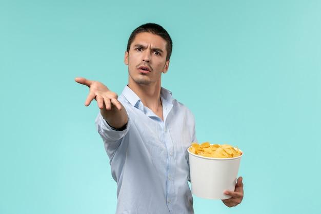Vue avant, jeune homme, tenue, panier, à, pomme terre cips, manger et regarder, film, sur, mur bleu, solitaire, télé, films, cinéma