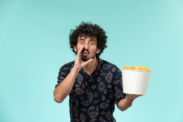 Vue avant, jeune homme, tenue, panier, à, pomme terre cips, sur, les, mur bleu clair, télécommande, cinéma, film, films, théâtre