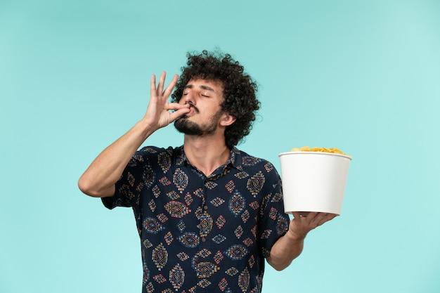 Vue avant, jeune homme, tenue, panier, à, pomme terre cips, sur, les, mur bleu, télécommande, film, cinéma