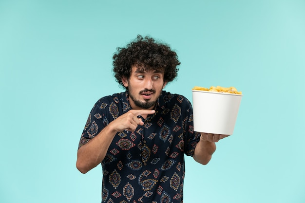 Vue avant, jeune homme, tenue, panier, à, pomme terre cips, sur, a, mur bleu, télécommande, films, cinéma, cinéma, théâtre