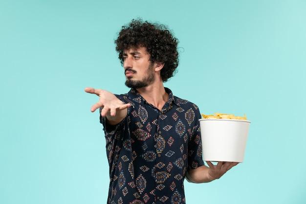 Vue avant, jeune homme, tenue, panier, à, pomme terre cips, et, regarder film, sur, les, mur bleu, cinéma, films, mâle, cinéma, théâtre