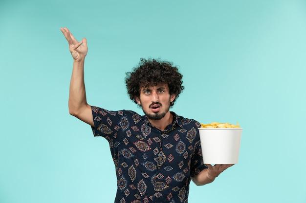Vue avant, jeune homme, tenue, panier, à, pomme terre cips, et, regarder film, sur, mur bleu clair, cinéma, films, mâle, cinéma