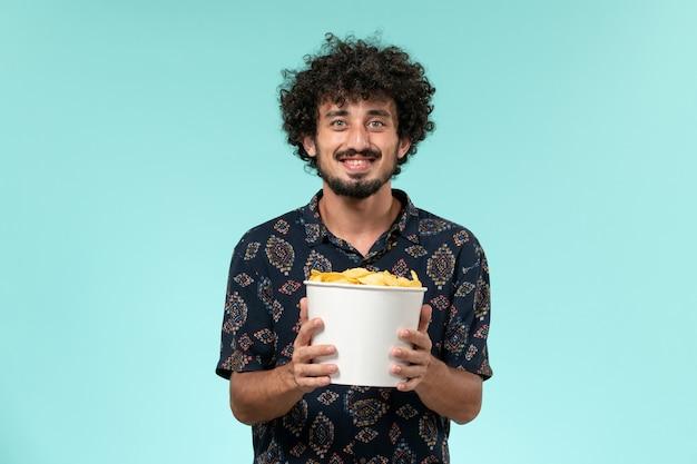 Vue avant, jeune homme, tenue, panier, à, pomme terre cips, et, regarder film, sur, mur bleu, film, cinéma, films, mâle, télécommande