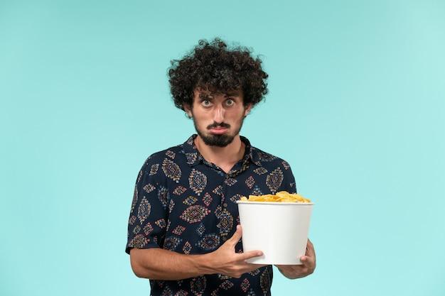 Vue avant, jeune homme, tenue, panier, à, pomme terre cips, regarder film, sur, les, mur bleu, télécommande, film, cinéma, films, théâtre