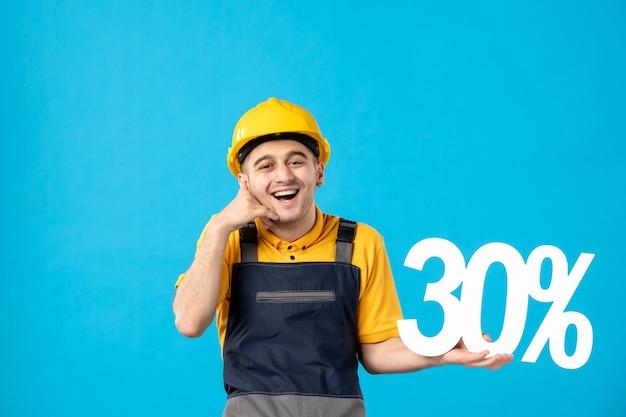 Vue avant joyeux travailleur masculin en uniforme avec écriture sur bleu