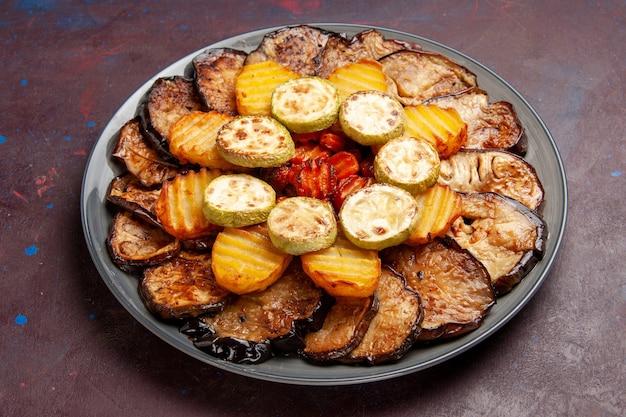 Vue avant des légumes cuits au four, pommes de terre et aubergines fraîchement sorties du four sur un espace sombre