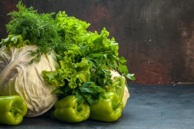 Vue avant de légumes frais chou persil poivrons laitue aneth chou-fleur sur surface isolée sombre