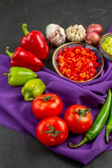 Vue avant des légumes frais avec du poivre et de l'ail sur fond sombre