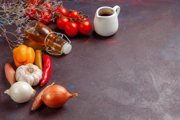 Vue avant des légumes frais avec de l'huile d'olive sur un bureau sombre