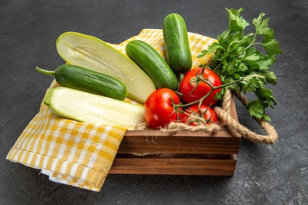 Vue avant de légumes frais tomates concombres courges et verts sur espace gris