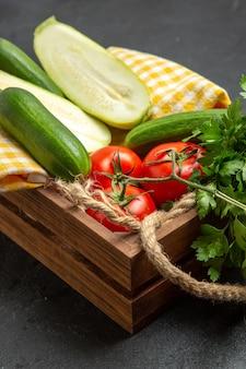 Vue avant de légumes frais tomates rouges concombres et courges avec des verts sur l'espace gris