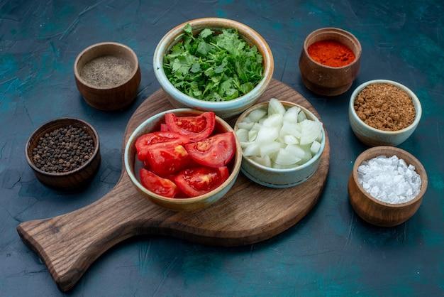 Vue avant des légumes frais tranchés, tomates et oignons avec des légumes verts et des assaisonnements sur un bureau bleu foncé légume repas dîner alimentaire