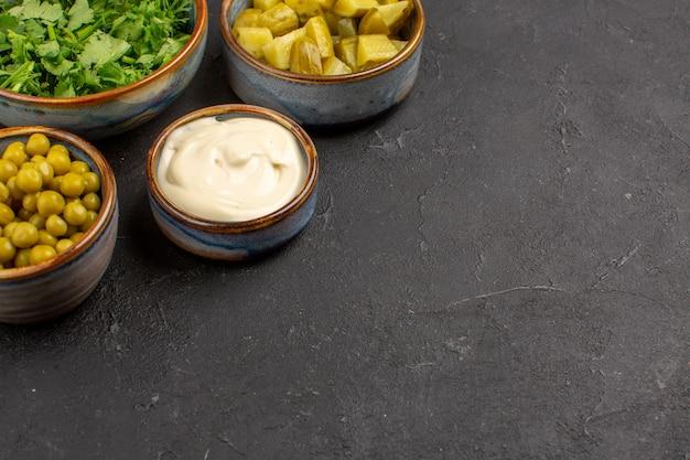 Vue avant des légumes verts et des haricots avec des cornichons sur une surface grise