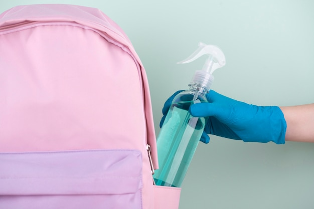 Vue avant de la main avec un gant chirurgical mettant une bouteille de désinfectant dans un sac de livre