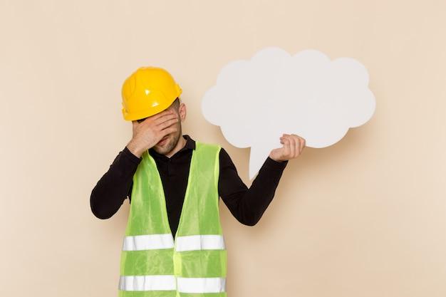Vue avant mâle constructeur en casque jaune tenant grand panneau blanc sur le fond clair