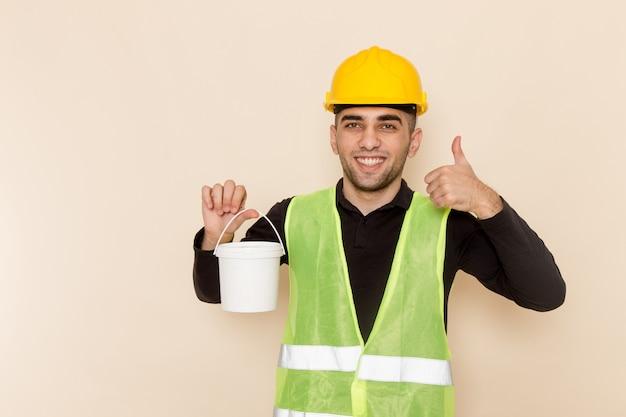 Vue avant mâle constructeur en casque jaune tenant de la peinture sur le fond clair