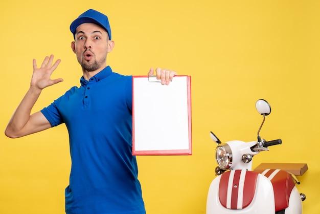 Vue avant male courrier holding file note sur couleur jaune travailleur service vélo travail émotion uniforme